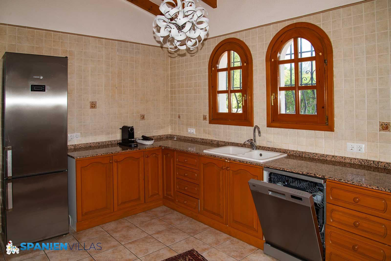 Kjøkken med hvitevarer i rustfritt stål.